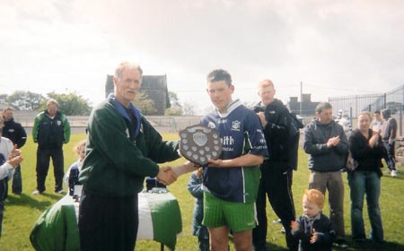 The Aodh Ruadh captain Kieran Kilgannon being presented with the Ernedale Height's Shield.
