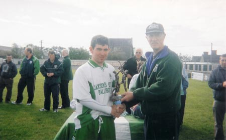 Martin 'Kerry' Ryan presenting the player of the tournament to Adam Gallinagh of McCumhaills.