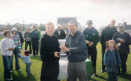 The Setanta captain, Richard Kee being presented with the Seamus Grimes memorial trophy.