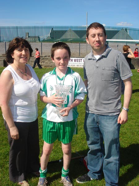 Kathleen and Eddie Grimes presenting the Aodh Ruadh captain Donal O'Keeffe with the Seamus Grimes Memorial Trophy.