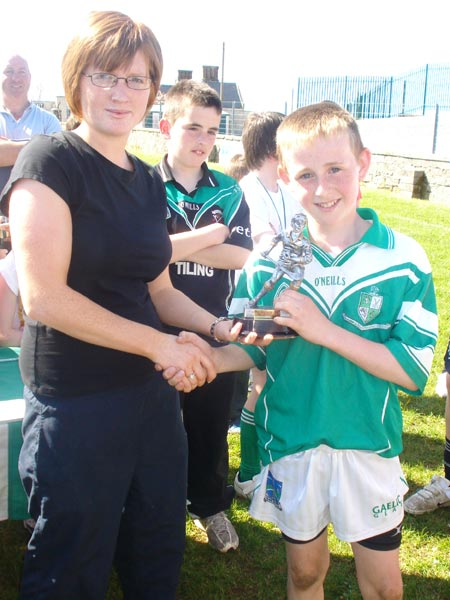 Caroline Ryan presenting the player of the tournament award to Kieran Corrigan from Lisbellaw.