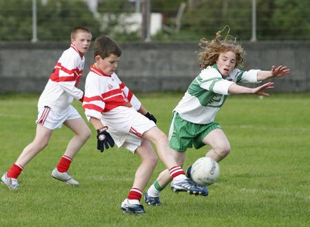 Matthew Ward of Dungloe clears his lines with Pauric Patton of Aodh Ruadh attempting the block.