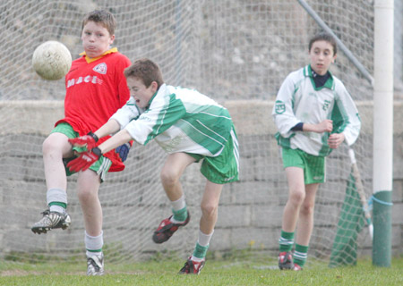 Kevin Warnock clears his lines under pressure from David McGurrin and Dominic Boyle.