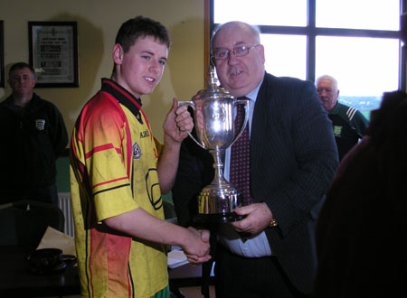 The winning Bakery Cup captain of 2007, Ronan McGurrin, receives the trophy from the winning Bakery Cup captain of 1957, Padraig McGarrigle.
