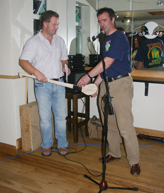 John Rooney, who organised the evening, presenting a hurl signed by both teams to Dennis.