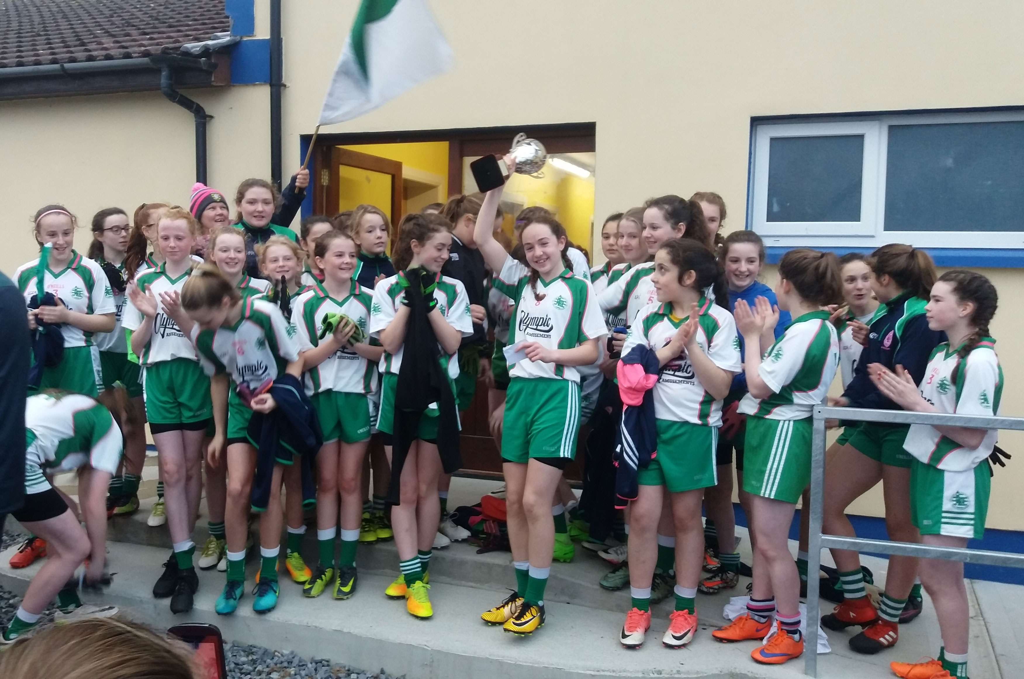 Aodh Ruadh captain Caoimhe Hughes-O'Brien raising the championship trophy.