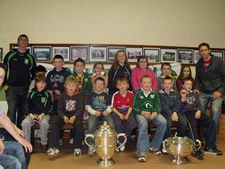 Under 10 squad with manager Michael Ayres and Michael Fennelly with Bob O'Keefe and National League trophies.