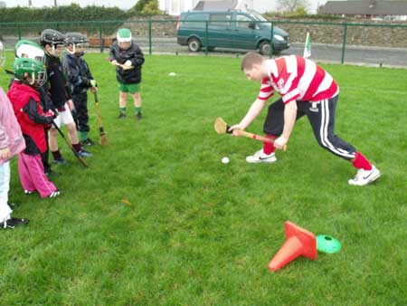 Shane Power demonstrating the roll lifts to attentive Aodh Ruadh under 8s.