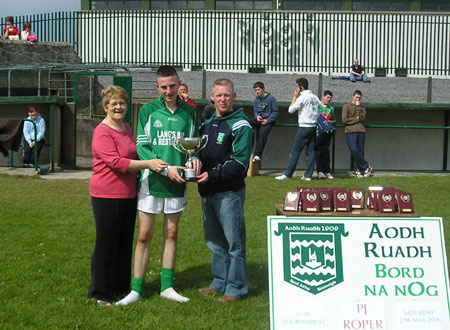 Mary Roper (left) and Brian Roper (right) present the PJ Roper trophy to James Brennan, the captain to the victorious Grange team, after the final of the PJ Roper under 16 tournament in Ballyshannon last Saturday.