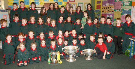 Pupils from Gael Scoil Ballyshannon pictured with the Sam Maguire, Tom Markham (All-Ireland minor football championship) and McKenna cups when they visited their school last Friday.