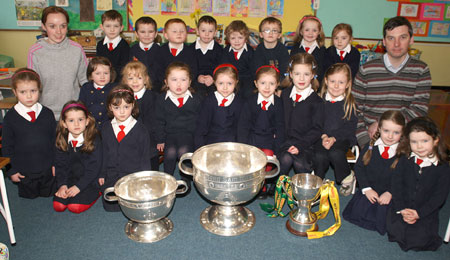 Junior Infants from Holy Family National School, Ballyshannon pictured with the Sam Maguire, Tom Markham (All-Ireland minor football championship) and McKenna cups when they visited their school last Friday.