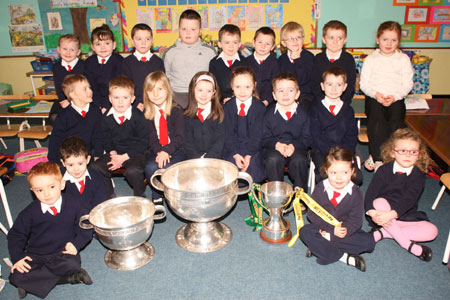Senior Infants from Holy Family National School, Ballyshannon pictured with the Sam Maguire, Tom Markham (All-Ireland minor football championship) and McKenna cups when they visited their school last Friday.