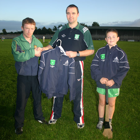 Packy McGrath of McGrath's Bouncy Castles presenting a set of track suits for the Aodh Ruadh under 12 hurlers to their manager, Peter Horan. Also present is the team's captain, Eugene Drummond.