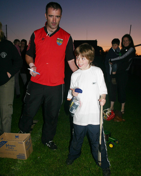 Stephen Lee, second place in the under 8 skills competition, accepting his medal from John Rooney.