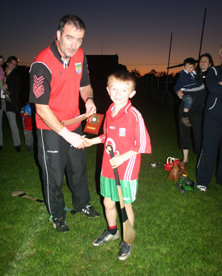 Liam O'Sullivan, winner of the under 8 skills competition, accepting his award from John Rooney.
