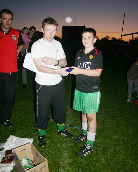 Peter Horan presenting Patrick Cassidy in medal for coming third in the under 10 skills competition.