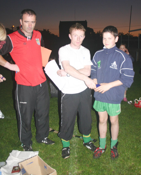 Peter Horan presents Colm Kelly with his medal for coming third in the under 12 skills competition.