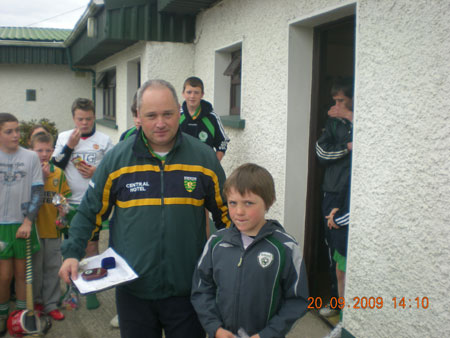 Eddie Lynch, under 8 manager, presenting Peader McHenry, sixth in the under 8 section with his medal.