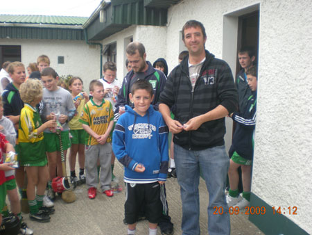 Michael Ayres, under 10 joint manager with Kevin McDermott in background, presenting Brian McHenry, sixth in the under 10 section with his medal.