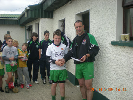 John Rooney, under 12 manager, presenting Conor Kennedy, fourth in the under 12 section with his medal.
