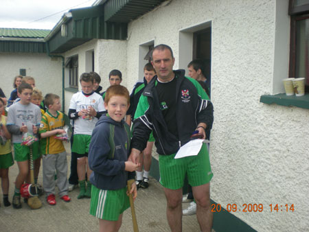 John Rooney, under 12 manager, presenting Shane McGrath, third in the under 12 section with his medal.