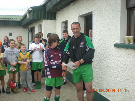 John Rooney, under 12 manager, presenting Oisín Rooney, first in the under 12 section with his medal.