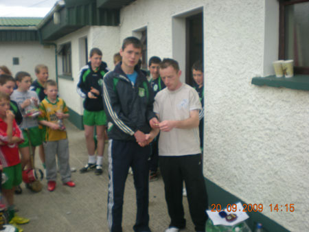Peter Horan, under 14 manager, presenting James Kelly, third in the under 14 section with his medal.