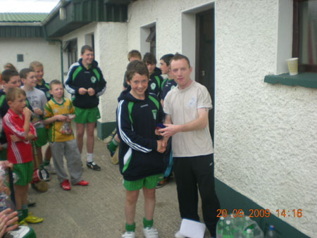 Peter Horan, under 14 manager, presenting Eddie Lynch, first in the under 14 section with his medal.