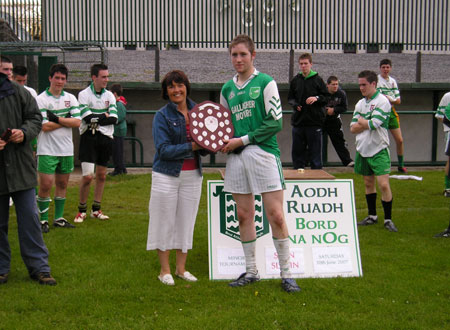 Sean Slevin's widow, Patricia, presents the Sean Slevin plaque to the victorious Bunninadden captain, Vincent Frizzell.