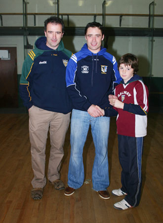 Alan Kerins, Galway senior hurling star, presents Oisin Rooney with his county under 12 hurling medal accompanied by mentor, John Rooney.