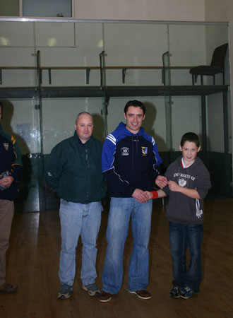 Alan Kerins presents Eddie Lynch with his under 12 hurling medal, accompanied by mentor, Eddie Lynch senior.