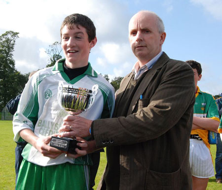 Johnny Gethins takes delivery of the under 14 championship trophy.
