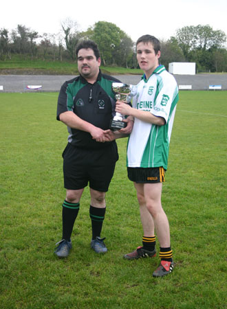Rory McGonigle, match referee and County Hurling Board Chairman, presents the Minor Hurling Trophy to the Aodh Ruadh caption, Stephen Ryan.
